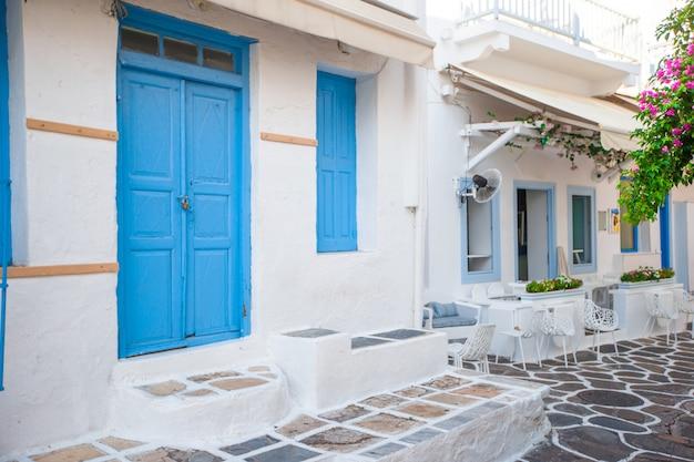 Узкие улочки острова с синими балконами, лестницами и цветами. красивая архитектура здания снаружи с кикладским стилем.