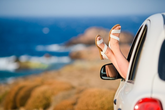 海の景色と車の窓から示す女性の足のクローズアップ