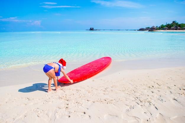 熱帯の休暇にビーチでの休暇中にサンタ帽子の少女