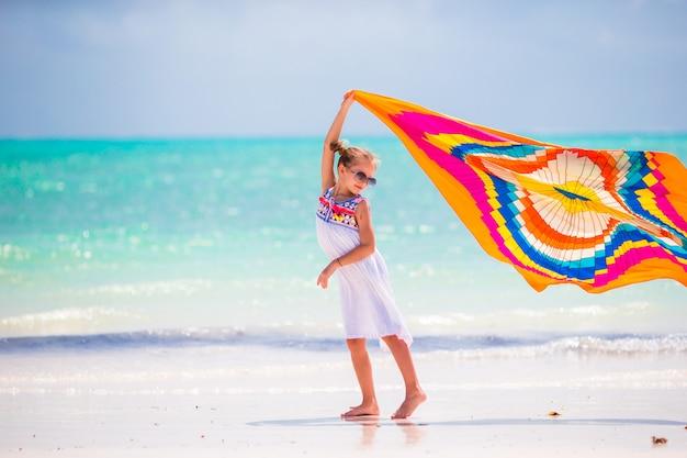 Маленькая девочка повеселиться с пляжным полотенцем во время тропического отпуска