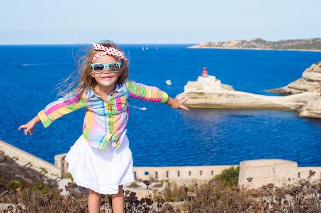 Очаровательная маленькая девочка на краю фона синего моря в бонифачо