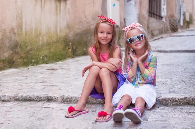 Очаровательные счастливые маленькие девочки на открытом воздухе в европейском городе
