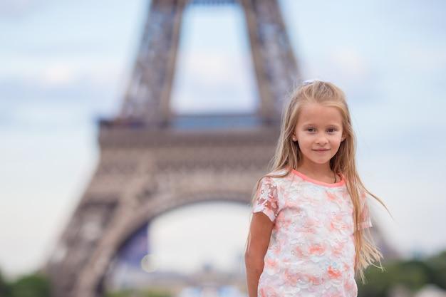 パリの愛らしい少女が夏休みの間にエッフェル塔を背景します。