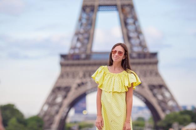 パリの美しい女性が夏休み中にエッフェル塔を背景します。
