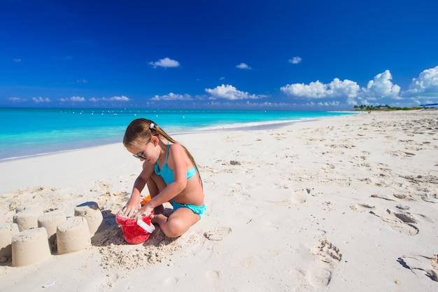 Прелестная маленькая девочка играя с игрушками пляжа во время тропических каникул