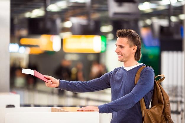 Молодой человек с паспортами и посадочными талонами на стойке регистрации в аэропорту