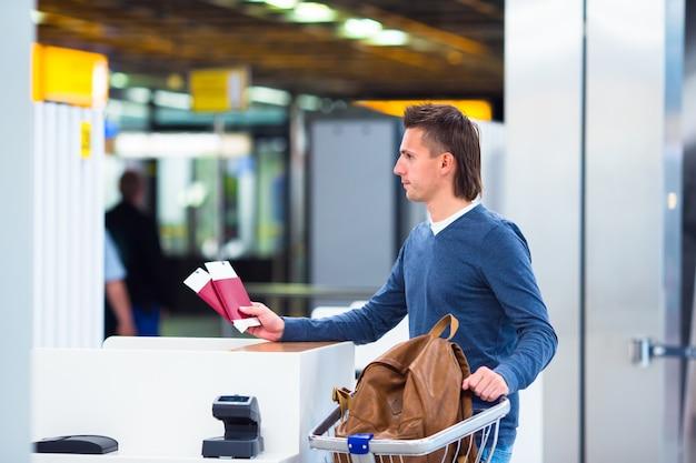 Молодой человек с паспортами и посадочные талоны на стойке регистрации в аэропорту