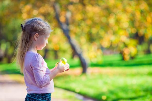 秋の日に美しい庭でアップルとのかわいい女の子