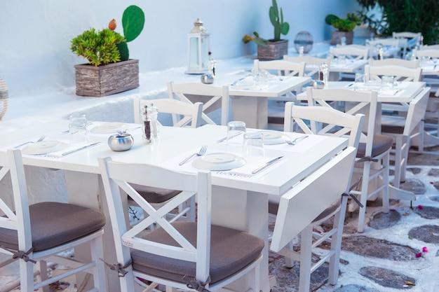 Белые столы со стульями в летнем пустом кафе на открытом воздухе
