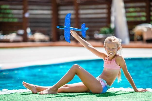 屋外プールの近くで楽しんで美しい少女