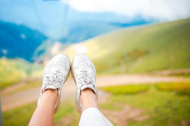 公園の屋外の芝生の上のスニーカーで女性の足のクローズアップ