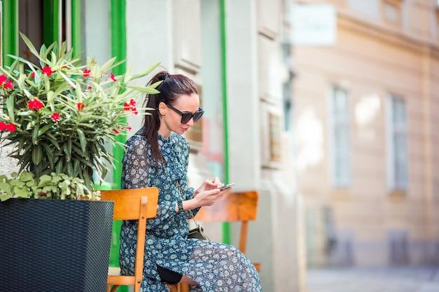 女性は街で彼女のスマートフォンで話します。イタリアの都市で屋外の若い魅力的な観光客