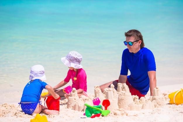 愛らしい少女と夏休みにビーチおもちゃで遊んで幸せな父