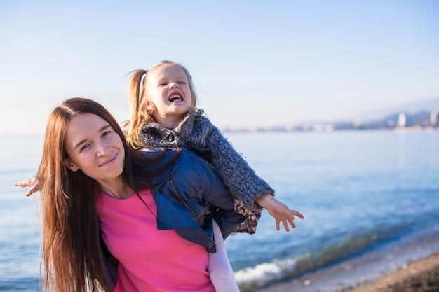 Маленькая девочка с мамой веселятся на пляже в зимний день