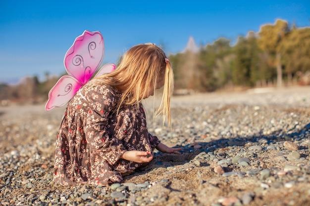 冬の晴れた日にビーチで遊ぶ愛らしい少女