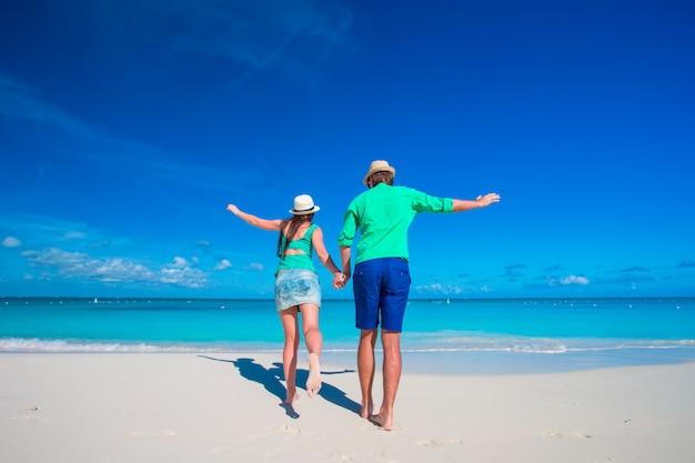 Молодая пара на белом пляже в летние каникулы