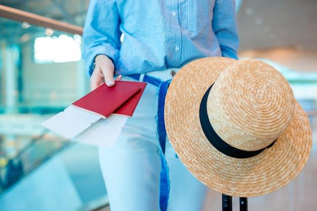 Крупным планом женщина, держащая паспорта и посадочный талон в аэропорту