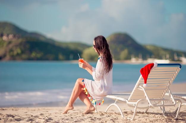 Отдыхая и наслаждаясь на летних каникулах, женщина, лежа на шезлонге на пляже