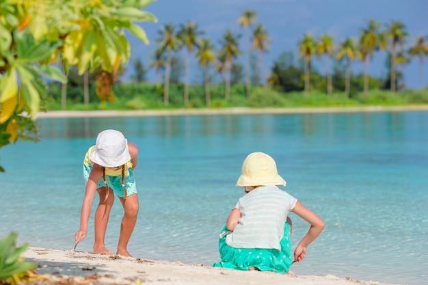 Маленькие очаровательные девушки рисуют картину на белом пляже