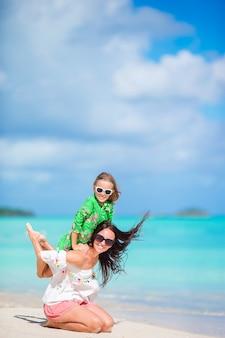 Красивая мать и дочь на карибском пляже, наслаждаясь летние каникулы.