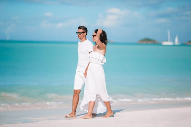 カリブ海のアンティグア島で白い砂浜とターコイズブルーの海の水と熱帯のビーチの上を歩く若いカップル