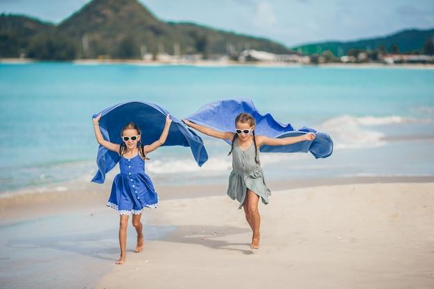 Маленькие девочки развлекаются с пляжным полотенцем во время тропического отпуска