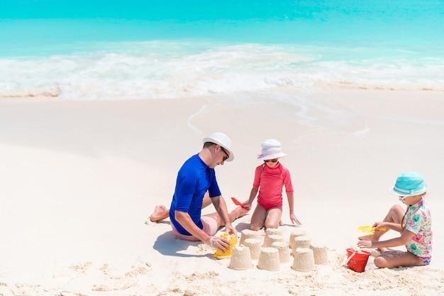 父と熱帯のビーチで砂の城を作る小さな娘