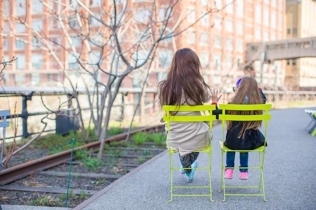 Очаровательная маленькая девочка и мама наслаждаются солнечным днем на нью-йоркской высокой линии