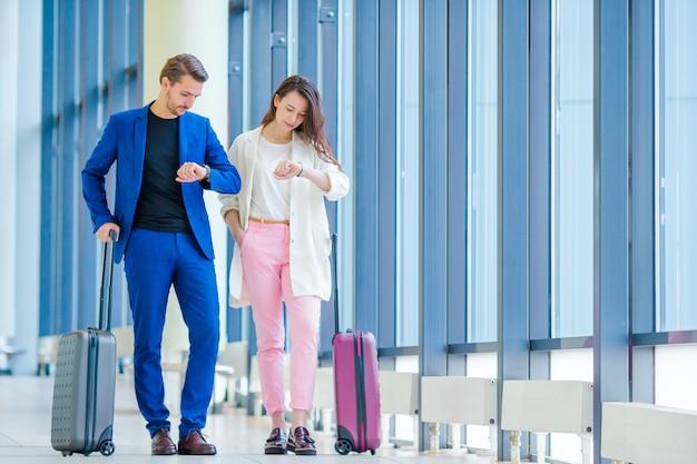 Пара с багажом в международном аэропорту спешит на рейс на посадку. мужчина и женщина смотрят на свои часы в помещении возле большого окна