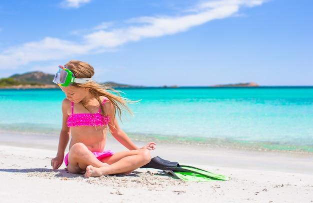 Маленькая девочка с ластами и очки для сснорклинга на пляже