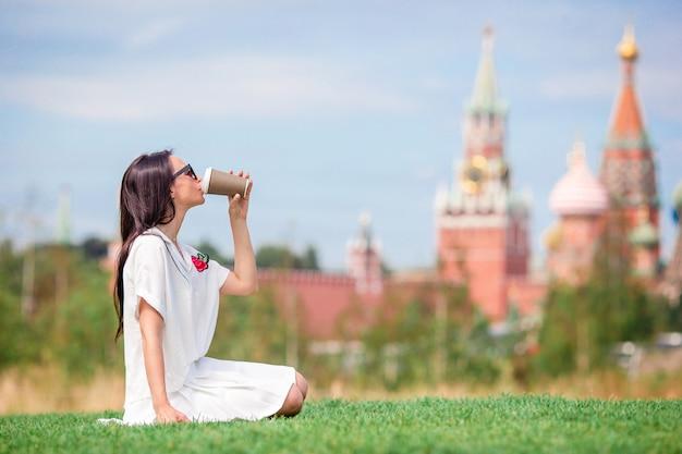 幸せな若い都市女ヨーロッパの都市でコーヒーを飲みます。