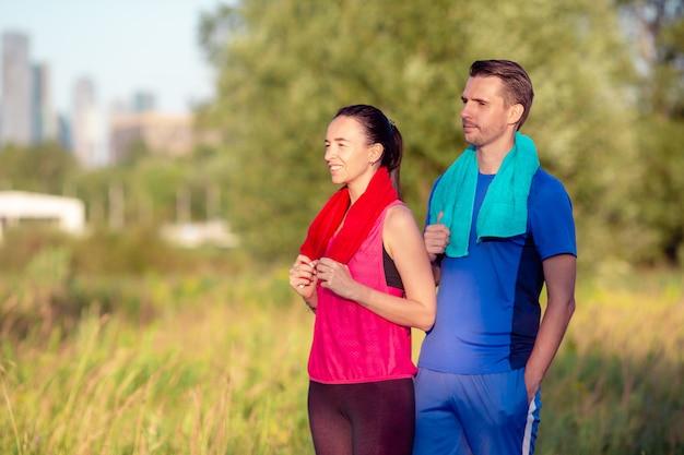 公園で走っているアクティブな陽気なカップル。健康と運動。