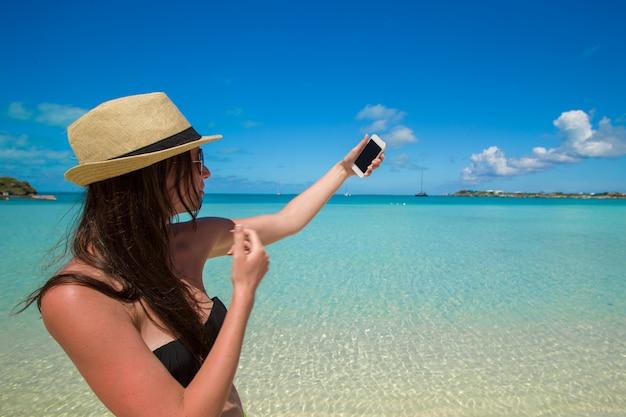 若い女性は熱帯のビーチで彼女の電話で写真を撮る
