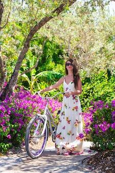 花の咲く庭園で自転車に乗って休暇中の若い女性