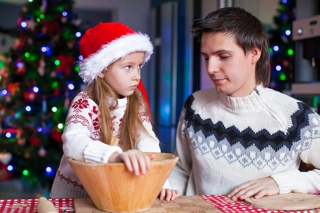 サンタ帽子の小さな娘と若いお父さんはジンジャーブレッドクッキーを焼く