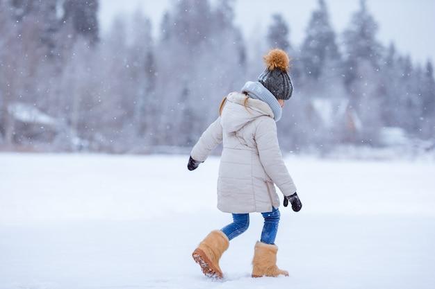 雪の晴れた冬の日の愛らしい少女の肖像画