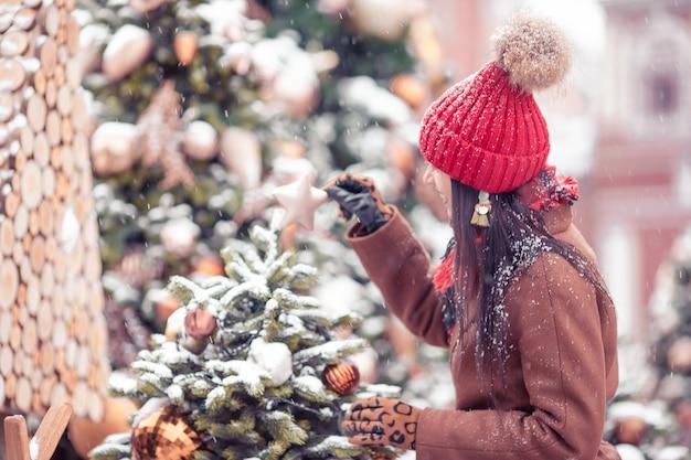 新年の雪の中でモミの木の枝の近くの幸せな女の子。