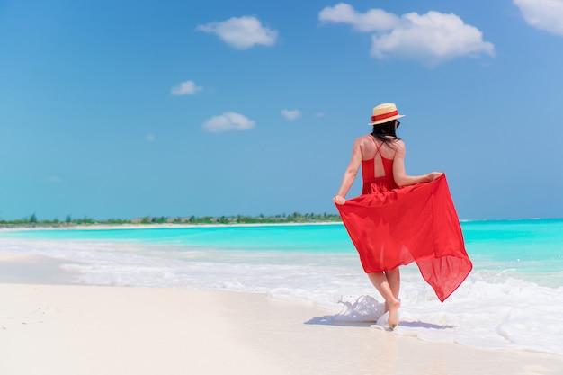 海岸の美しい赤いドレスの少女