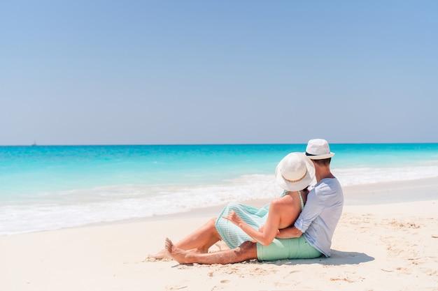 夏休みの間に白いビーチで若いカップル。幸せな恋人たちは新婚旅行を楽しみます