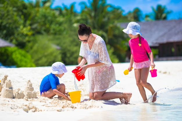 愛らしい少女と夏休みにビーチおもちゃで遊んで幸せな母