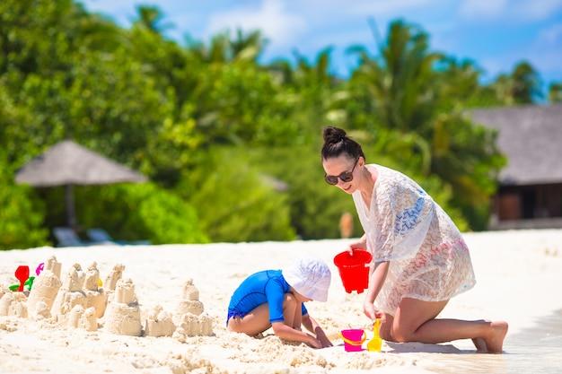 小さな女の子と夏休みにビーチおもちゃで遊んで幸せな母