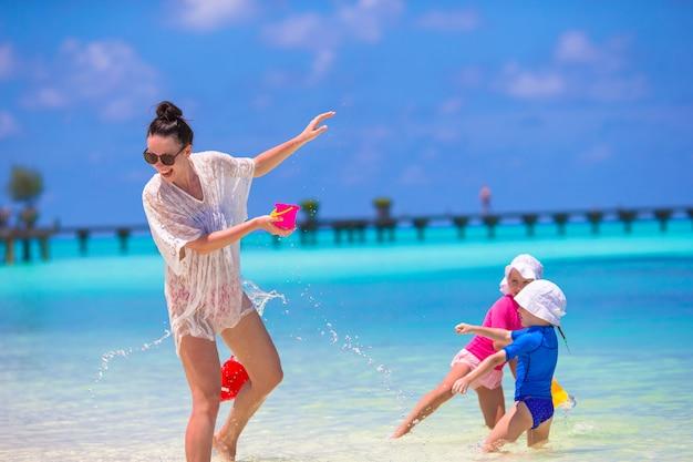 若いママと夏のビーチでの休暇中に楽しんでいる小さな女の子