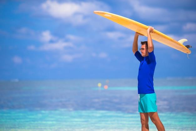 熱帯の海岸でサーフィン幸せな若い男