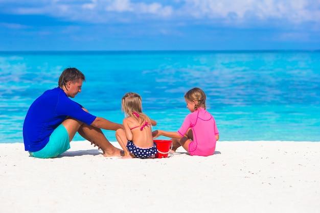 愛らしい女の子と夏休みにビーチおもちゃで遊んで幸せな父
