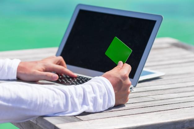コンピューターとテーブルの上のクレジットカードのクローズアップ