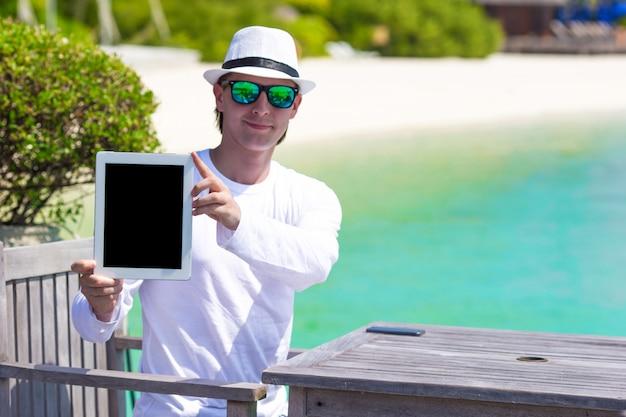 熱帯のビーチでの休暇中にタブレットコンピューターと若い男