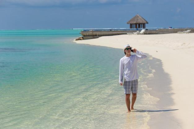 熱帯のビーチで携帯電話で話している若い男