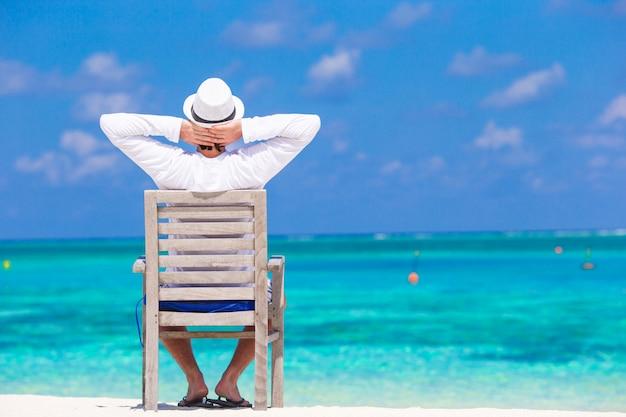 熱帯のビーチで夏休みを楽しんでいる若い男
