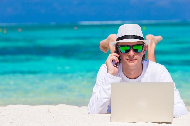タブレットコンピューターと熱帯のビーチでの携帯電話と若い男
