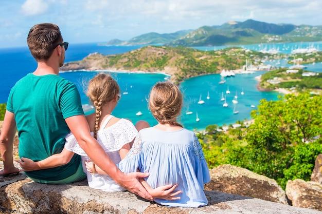Очаровательные маленькие дети и молодой отец, наслаждаясь видом на живописную английскую гавань в антигуа в карибском море